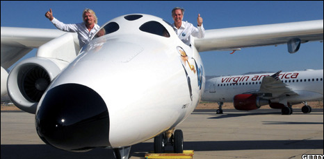 Richard Branson (L) and Burt Rutan wave during the official launch of Virgin Galactic's White Knight Two