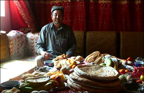 Chong Mehmet sits at a table covered with food (Image: Hugh Sykes)