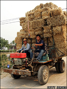 Chinese farmers transporting bales of straw (Getty Images)