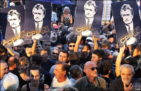 Protesters in Belgrade holding Radovan Karadzic placards