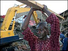 Rescue workers at the site of a collapsed building in Abuja