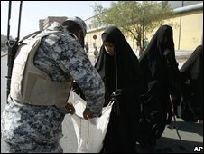 An Iraqi police officer searches bags of female pilgrims in Baghdad, Iraq (28/07/2008)