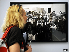 "A woman looking at a photograph by Helmut Newton in the exhibition ""Pigozzi and the Paparazzi"""