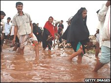People walk through a river to get into town July 25, 2008 in the port city of Chittagong, Bangladesh