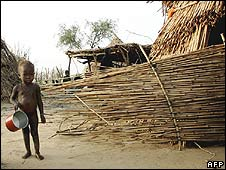 A boy stands in front of his hut in southern Niger