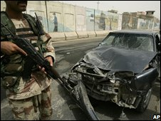 An Iraqi army soldier stands next to a vehicle damaged in a roadside bomb blast in Baghdad, Iraq (30/07/2008)