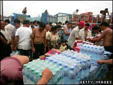 People wait to receive food and water at a temporary settlement in Mianzhu on 19 July 2008