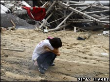 A woman cries in front of a collapsed building in Beichuan, Sichuan province on 19 July 2008