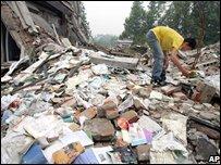 Man sifting through school wreckage