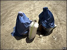 Two Afghan women receive their monthly aid ration from an international aid agency near Kabul (image: 29 June 2008)