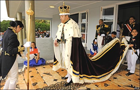 King George Tupou V wears a maroon-coloured cape trimmed with white ermine fur and a three-metre train carried by child pages as he emerges from his coronation in Nuku'alofa on Friday