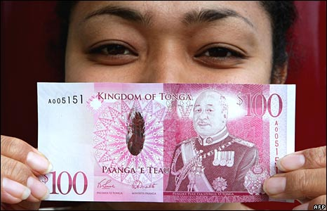 Reserve Bank of Tonga clerk Selaima Finau displays the just released one hundred pa'anga note featuring the new monarch