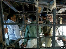 Railway officials inspect the wreckage of the train which caught fire in Andhra Pradesh