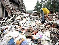 Boy examining wreckage of collapse Juyuan Middle School