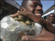 A man carries a bag filled with old Zimbabwean coins to a bank in Harare 