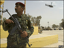 Iraqi soldier on patrol as US helicopter flies overhead