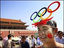 A man wears the Olympic rings on his head in Tiananmen Square, Beijing, China