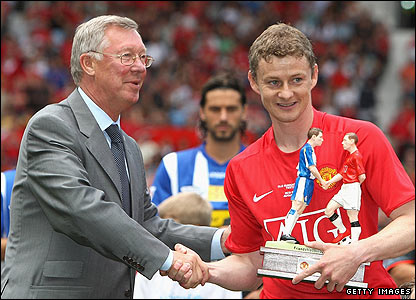United boss Sir Alex Ferguson presents Solskjaer with a trophy to mark the occasion