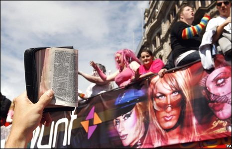 A protester holds up a bible as the Pride parade passes in Belfast City Centre