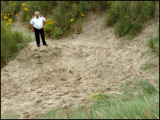 Coastguard John Jones on the top of the sand dune where a young boy died in Cefn Sidan beach, Pembrey