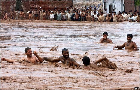 Pakistani volunteers rescue villagers in a flooded area on the outskirts of Peshawar