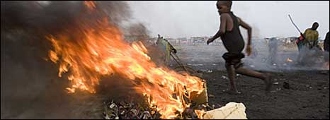 A child running past burning cables at a computer dumpsite in Ghana (Copyright: Greenpeace)