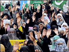 Female activists of Sunni Muslim group Jemaah Islamiah chant slogans against the US and Pakistani President Pervez Musharraf during a protest in Karachi on July 31, 2008