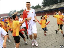 Chinese Olympic basketball star Yao Ming is mobbed by fans after his leg of the relay