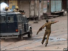 Policeman throws a stone at protesters in Srinagar 
