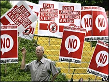 Man stands under posters placed outside the Venezuelan Supreme Court