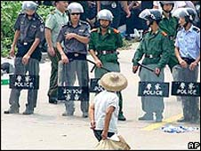 A villager walks past a row of riot police in Taishi village on 12 September 2005