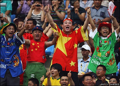 Fans cheer during the women's group F games in Shenyang