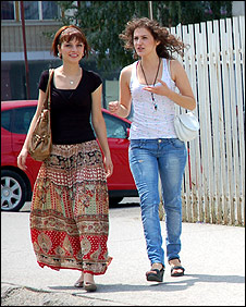 Two young women walk down a Pristina street 
