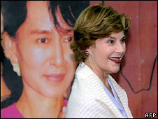 Laura Bush stands in front of a poster of Aung San Suu Kyi during her visit to the refugee camp