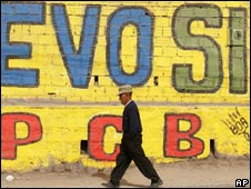 "A man walks past a wall in La Paz reading ""Evo Yes"""