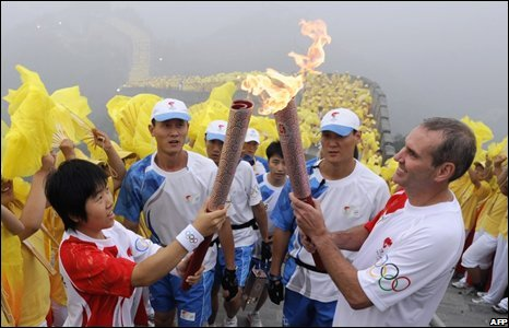 Wang Ning (L) passes the flame to Briton Colin Giles, 07/08
