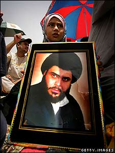 A supporter of Moqtada Sadr holds a picture of the Shia cleric (July 2008)