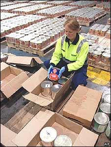 A customs agent unpacks tins disguised as canned tomatoes holding thousands of ecstasy tablets in Melbourne, Australia