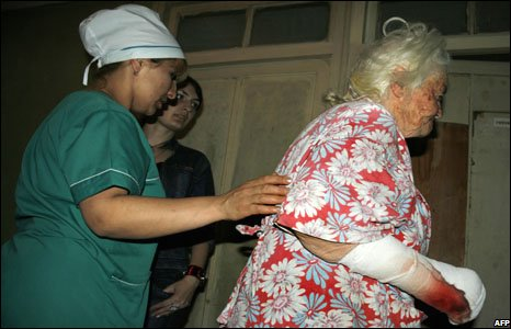 A nurse helps an elderly woman injured during the armed conflict between Georgian and South Ossetian separatist forces in Tskhinvali 7 August 2008
