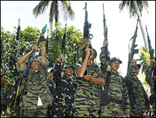 Muslim guerrillas of the Moro Islamic Liberation Front (MILF) raise their weapons during a formation in Camp Darapanan, the rebel base in southern Maguindanao province on Wednesday