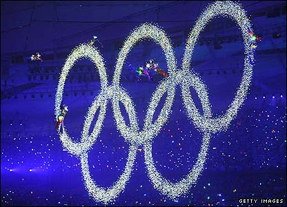 The Olympic rings are hoisted into the night sky
