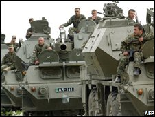 Georgian troops ride in armoured personnel carriers