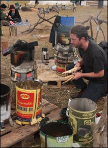 Campers boil the kettle on cookers made from old cooking oil tins