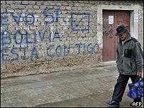 Hombre pasa frente a una pared con un graffiti en apoyo a Evo Morales.