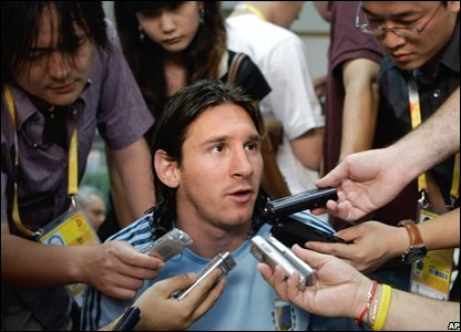 Lionel Messi surrounded by reporters