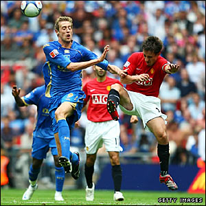 Portsmouth's Peter Crouch (left) and Manchester United's Gary Neville challenge for the ball