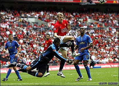 Pompey keeper David James beats Manchester United's Darren Fletcher to the ball