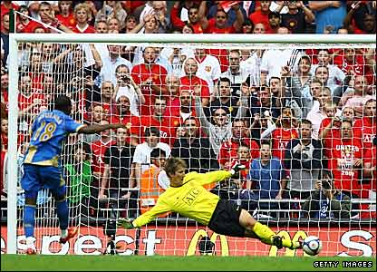 Manchester United's Edwin van der Sar saves from Arnold Mvuemba