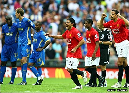 Portsmouth players are dejected while Manchester United's players celebrate after winning the Community Shield