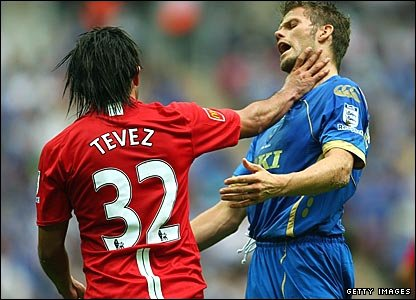 Manchester United's Carlos Tevez grabs Portsmouth's Hermann Hreidarsson